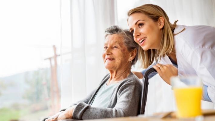 elderly woman in nursing home sitting in wheelchair with blonde female caretaker behind her
