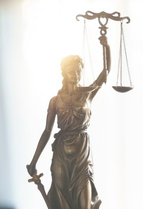 Lady Justice statuette with bright light behind it